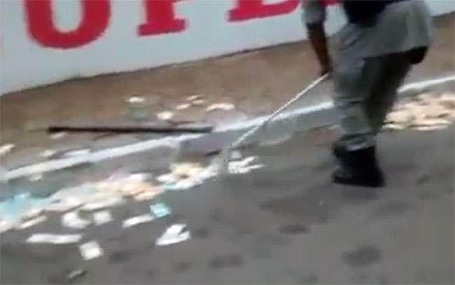 Policiais varrem rua para juntar dinheiro espalhado após roubo de caixa eletrônico