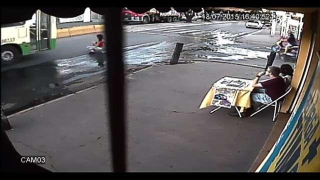 Mulher escorrega em avenida e escapa de atropelamento