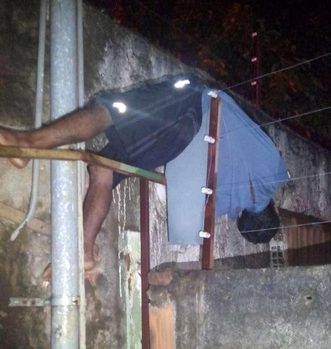 Homem tenta roubar casa, leva choque e fica pendurado em muro