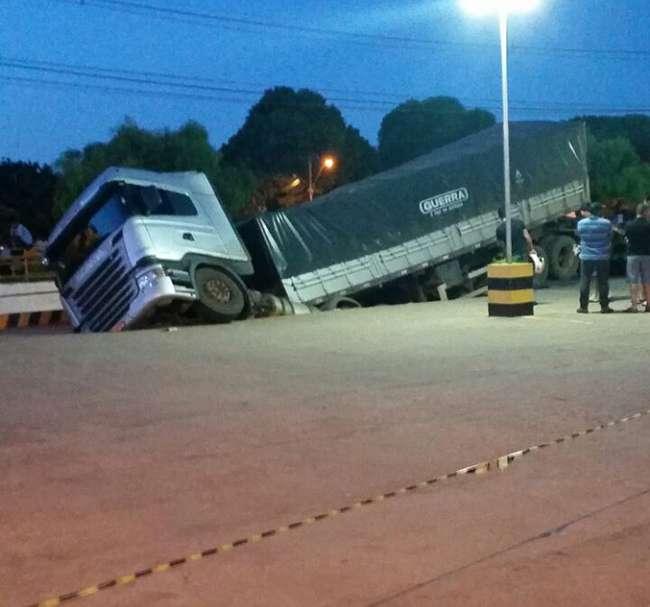 Chão cede e deixa caminhão suspenso em estacionamento