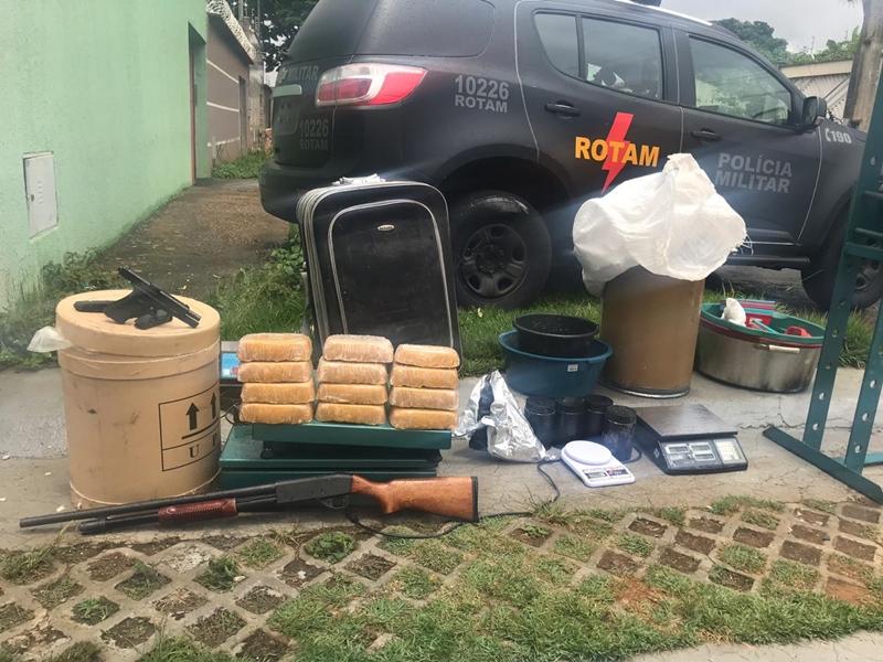 Apreensão: Uma espingarda calibre 12, pistola de uso restrito, drogas e insumos para refino (Foto: Divulgação/ PM)