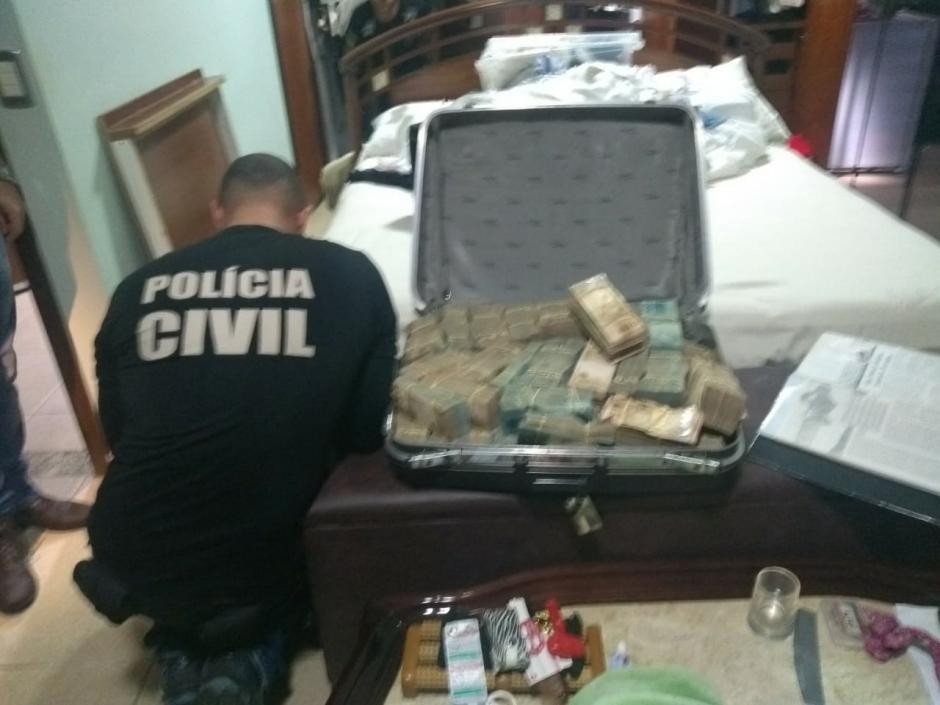 Dinheiro e pedras preciosas são encontrados pela Polícia Civil escondidos dentro de porão que era fechado no fundo falso de um guarda roupas (Foto: PC-GO)