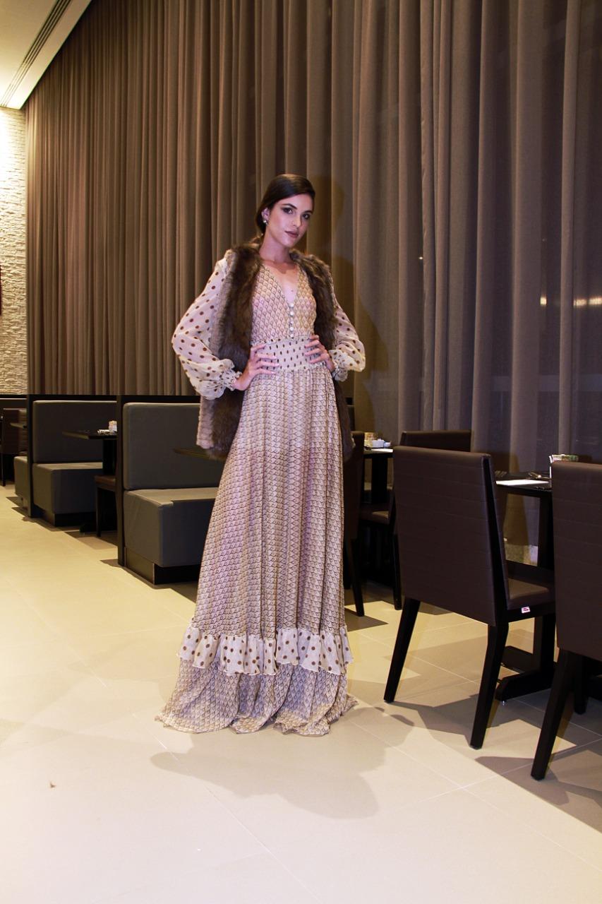 O vestido fluido e esvoaçante, transparente, é complementado com colete de pele e joias da Liane Campos (Foto: Marcos Zapp)