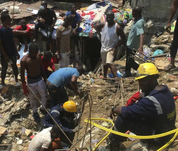 Equipes de resgate e populares tentam retirar crianças de escombros de prédio que abrigava escola primária em Lagos, capital financeira do país (Foto: AP Photo/Sunday Alamba)