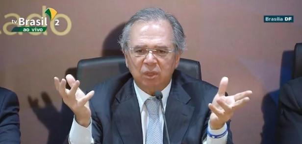 O ministro Paulo Guedes em coletiva com a pulseira em referência ao versículo búblico Apocalipse | Reprodução Youtube