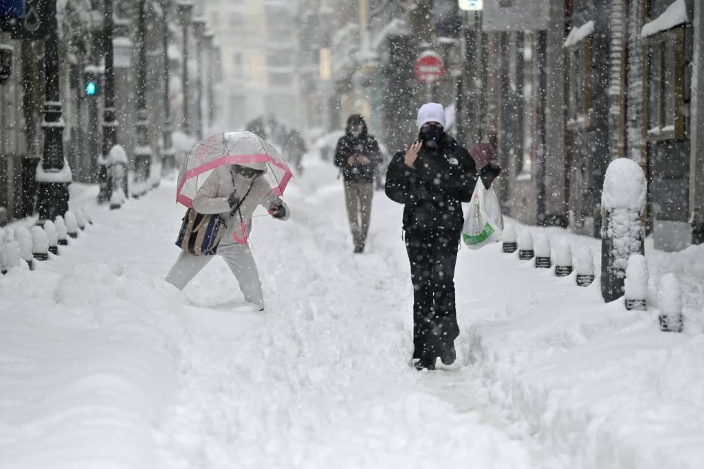 Pessoas andam pelas ruas de Madri, em meio a forte nevasca que atinge o país (Foto: AFP)