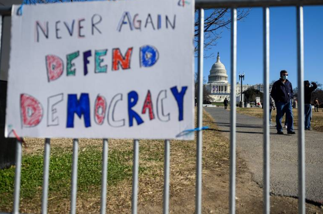 """Cartaz com a frase """"nunca outra vez, defenda a democracia"""" em grade que cerca o Capitólio (Foto: Andrew Caballero / AFP)"""